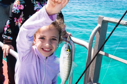 Child fishing on boat around Rottnest Island